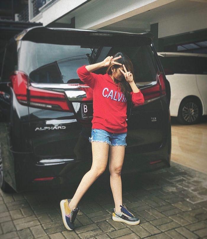 Penampilan Ayu Ting Ting saat foto berpose di depan mobil mewah