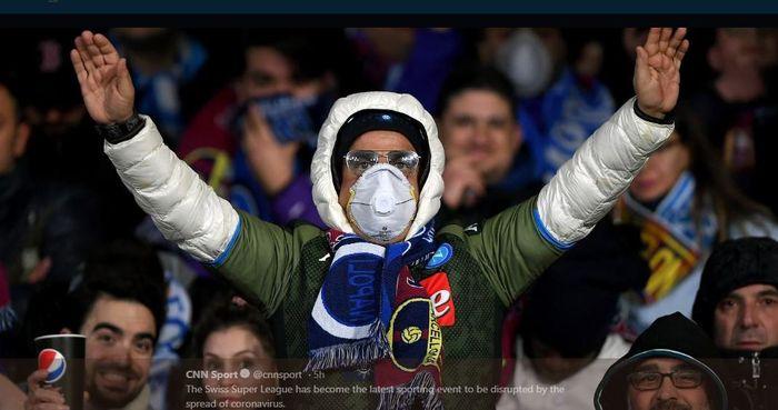 Pendukung Napoli menggunakan masker dalam pertandingan Liga Champions melawan Barcelona di Stadion San Paolo.
