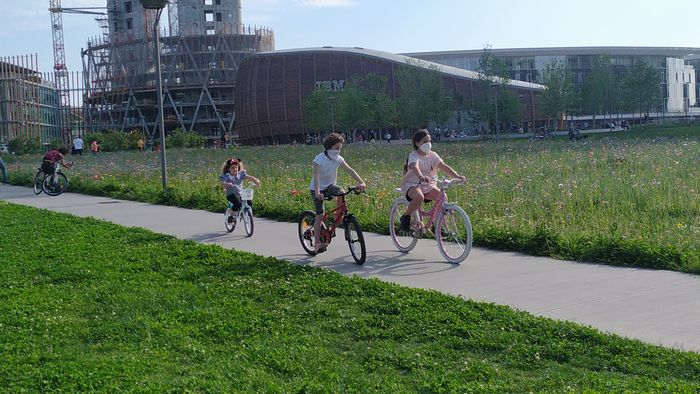 Suasana hari-hari akhir karantina—minggu pertama Mei 2020—di Milan, Italia. Anak-anak mulai bermain dan bersepeda di ruang publik, meski masih harus mengenakan masker.
