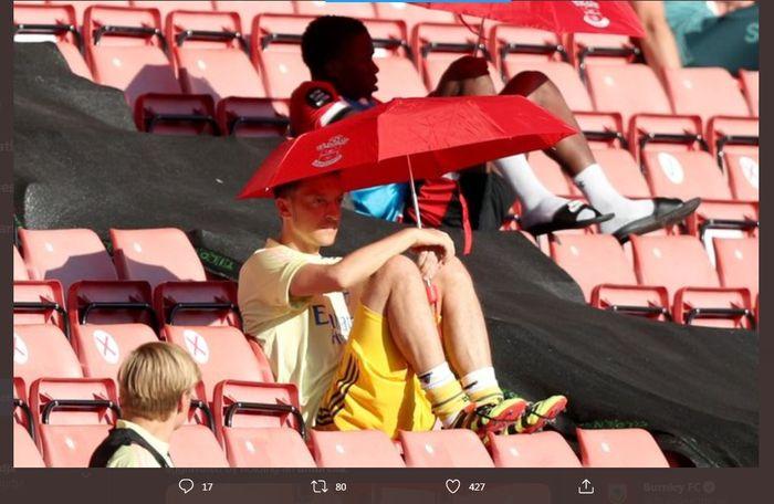 Mesut Oezil menyaksikan laga Arsenal dari bangku penonton dengan memakai payung.