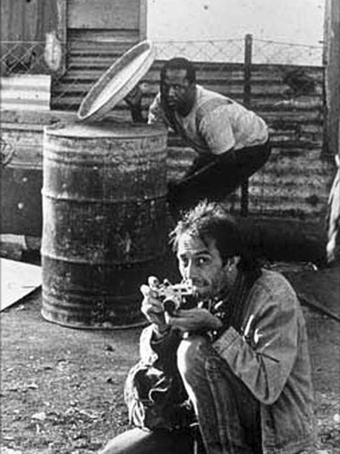 Wartawan foto Guy Adams mengambil foto Carter ini selama kekerasan di kota, seorang lelaki menggunakan tutup tempat sampah sebagai perisai.