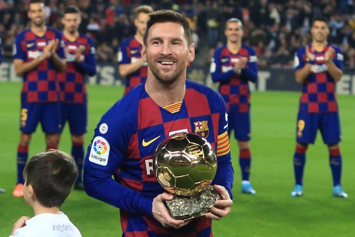 Bintang FC Barcelona, Lionel Messi, berpose dengan trofi Ballon d'Or. Messi memutuskan bertahan di Barcelona untuk musim 2020-2021.