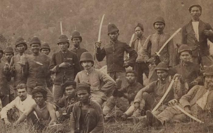 Letnan Satu T.J. Veltman bersama brigade Marechaussee dan porter mereka di Aceh Besar, 1898. Fotografer: C.B. Nieuwenhuis .