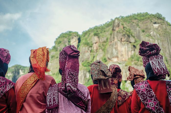 Several women in traditional dress are watching one of the performances of the Pasa Harau Art & Culture Festival in the Harau Valley.