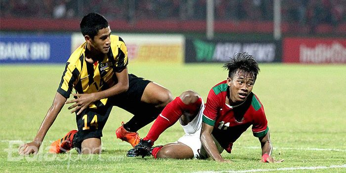 Gelandang timnas U-16 Indonesia, Mochammad Supriadi (kanan), dilanggar pemain Malaysia pada l