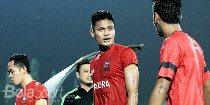 Pemain belakang Madura United, Fachruddin Aryanto (tengah), berbicara dengan rekan setimnya usai l