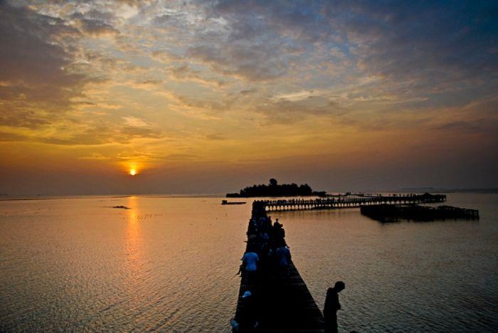 Pemandangan matahari terbenam di jembatan Pulau Tidung, Kepulauan Seribu, Jakarta. Jembatan yang men