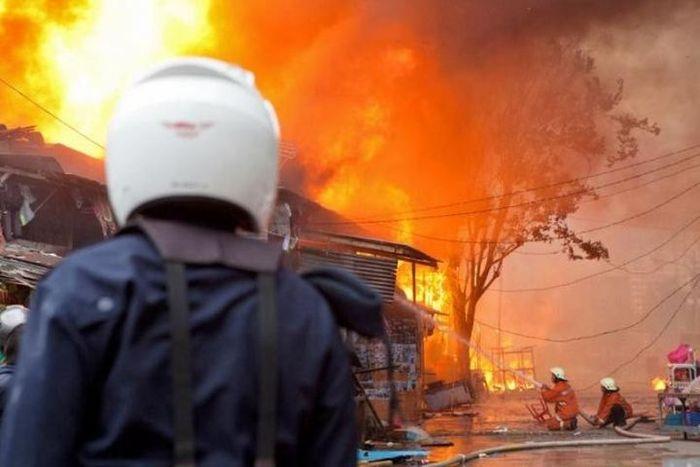 Dua petugas pemadam kebakaran mengarahkan air ke api yang sudah membesar pada sebuah kebakaran di Ja