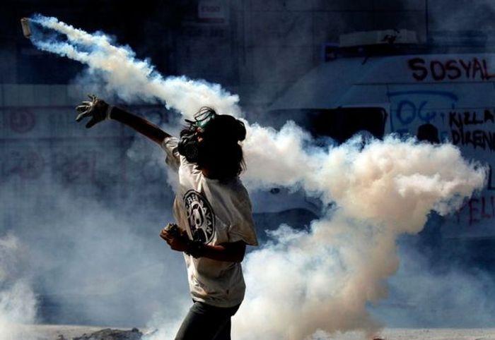 Demonstran di Alun-alun Taksim, Istanbul, Turki, mengembalikan gas air mata pada polisi..