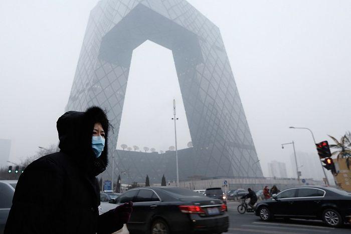 Seorang perempuan di Beijing menggunakan masker akibat polusi udara.