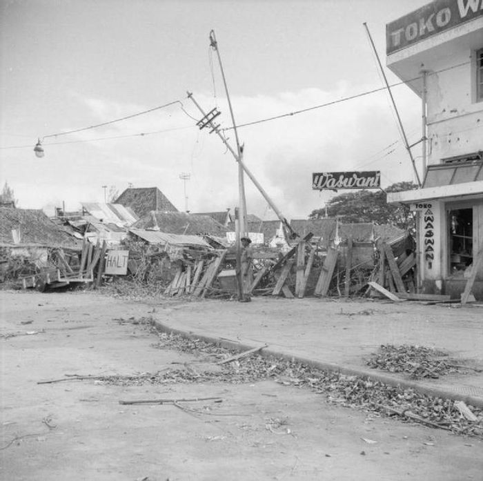Pemandangan kota usai pemboman besar-besaran oleh Inggris. Seorang serdadu India berjaga di jalanan yang dikuasai pihak militer Inggris di Kota Surabaya.