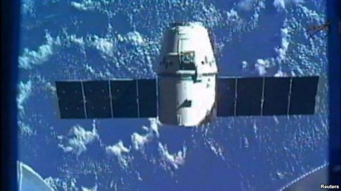 Pesawat kargo SpaceX, Dragon, terlihat di ujung tangan robot Canadarm2 ISS pada pengiriman pasokan a