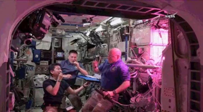 Tiga orang astronaut tengah menyantap sayur selada, sayur pertama yang berhasil ditanam di ISS.