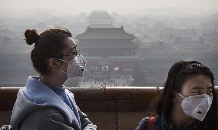 Wanita Cina memakai masker karena kabut asap yang disebabkan oleh polusi udara.