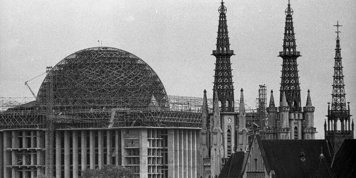 Foto Kubah Masjid Istiqlal yang belum selesai dibangun, dengan latar belakang Gereja Katedral.