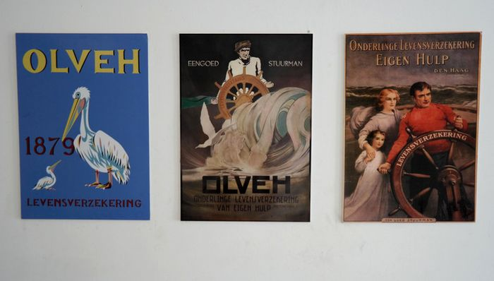 Tiga poster yang merupakan replika iklan perusahaan asuransi OLVEH, yang dipajang di lantai dasar gedung itu.
