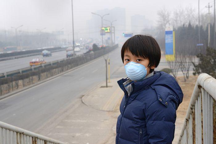 Seorang anak laki-laki menggunakan masker untuk mengurangi efek polusi udara di Beijing, Tiongkok.