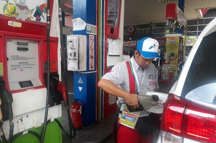 Ilustrasi petugas SPBU Pertamina tengah mengisi BBM ke mobil konsumen