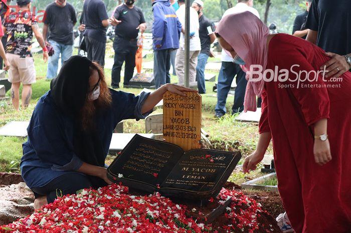 Istri dari almarhum Ricky Yacobi, Harly Ramayani (baju biru), nampak duduk didekat makam sang suaminya di TPU Tanah Kusir, Jakarta Selatan, 21 November 2020