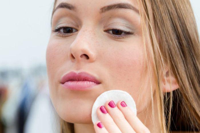Ilustrasi perempuan bersihkan wajah dengan kapas (Freepik)