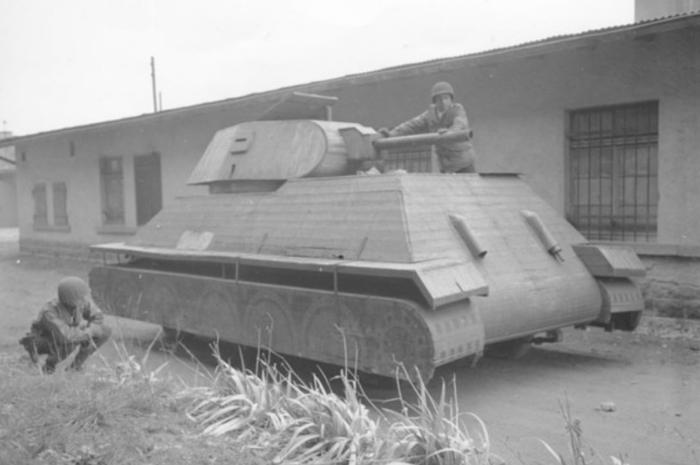 Dua orang tentara Amerika memerika sebuah tank tiruan milik Nazi Jerman yang terbuat dari kayu dan tripleks.