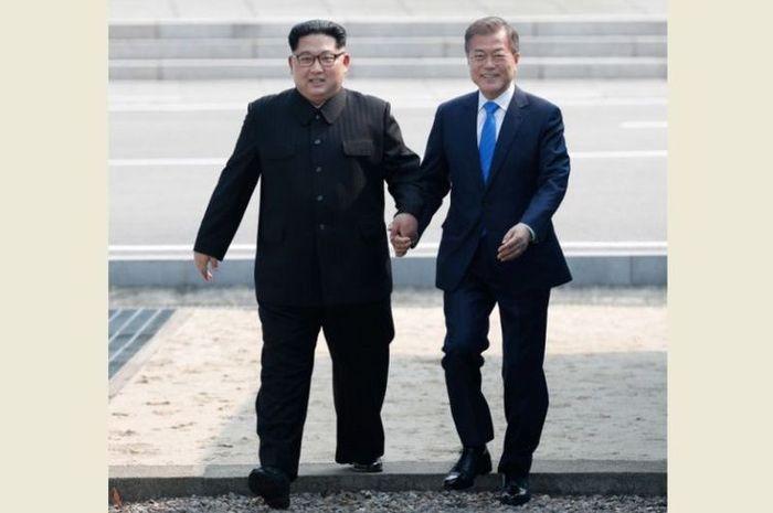 Pemimpin Korea Utara Kim Jong Un (kiri) dan Presiden Korea Selatan Moon Jae-in (kanan) berpegangan tangan
