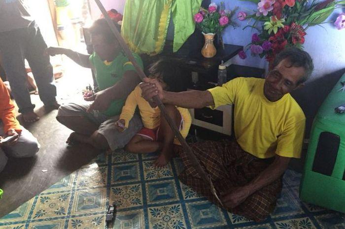 Munsa (kanan) dan Johar (kiri) menunjukkan tombak yang digunakan oleh keluarganya untuk memburu duyung.