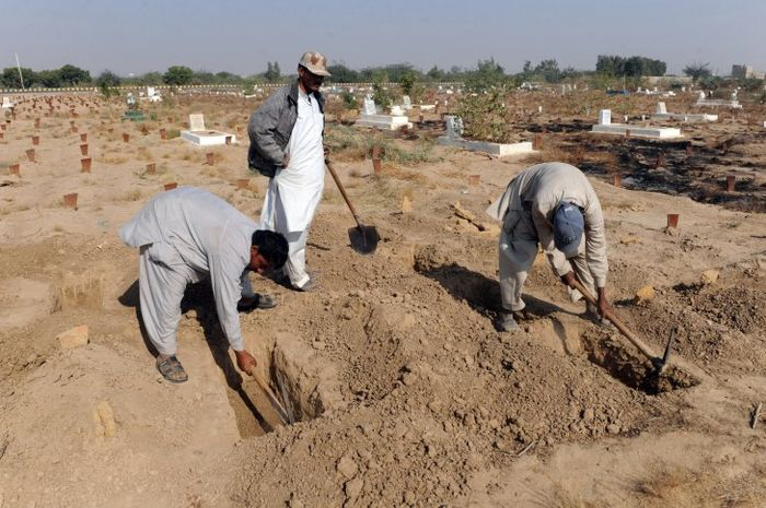 Para sukarelawan menggali kubur untuk bayi-bayi yang ditemukan tak bernyawa
