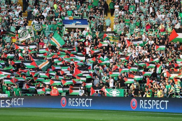Para suporter yang meregangkan bendera Palestina
