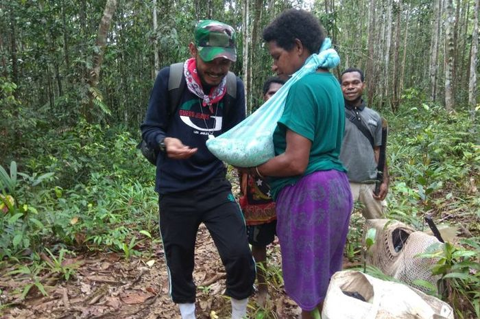 Perawat Tim Nusantara Sehat, Merixz, memberikan imunisasi di tengah hutan kepada seorang bayi berusi