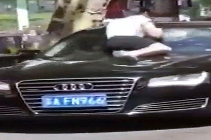 istri yang marah naik ke kap mobil suaminya yang sedang berjalan