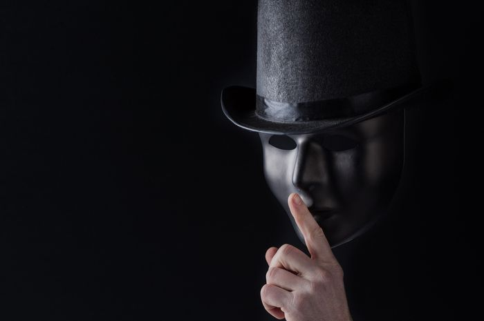 Male finger showing shh sign on black mask wearing black top hat on black background with copy space. Freedom of speech and silence concept