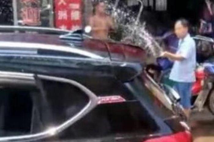 Pemilik toko dan pejalan kaki menyemprotkan air pada mobil agar seorang anak yang terkunci di dalamnya tidak kepanasan.
