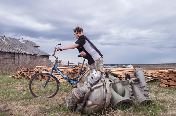 Remaja Rusia berdiri di dekat potongan roket.