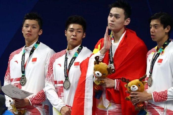 Sun Yang berselubung bendera saat terima medali sementara rekan-rekannya mengenakan jaket