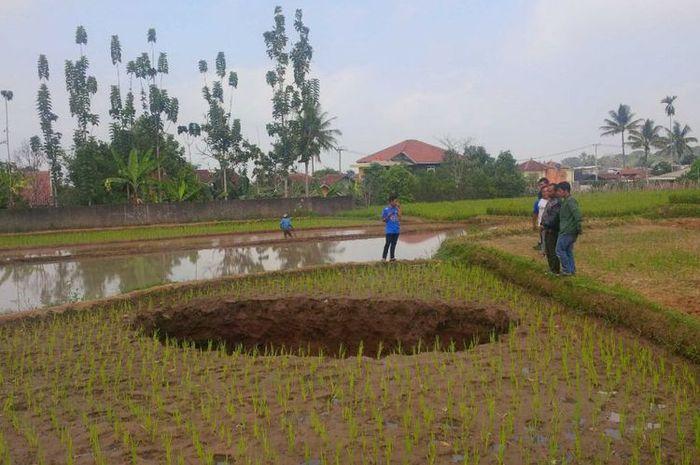 Sejumlah warga melihat tanah ambles berbentuk bulat di Kadudampit, Sukabumi, Jawa Barat. (KOMPAS.com/BUDIYANTO)