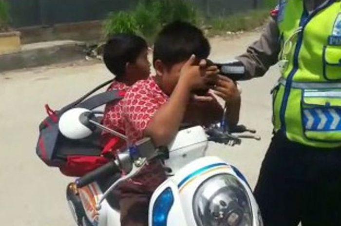 Dua bocah SD menangis sambil membujuk dan terus mencium tangan polisi agar ia dibebaskan dari tilang polisi.(Screenshot Facebook)
