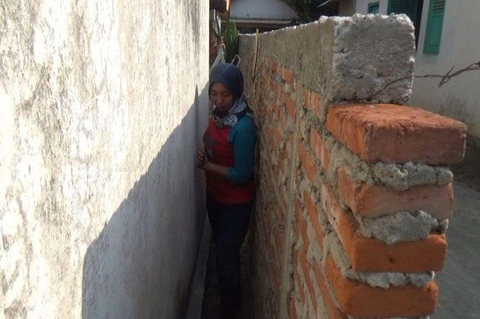 Siti Khotijah, warga Desa Sudimoro, Megaluh, Jombang, Jawa Timur, saat keluar dari rumah melalui cel