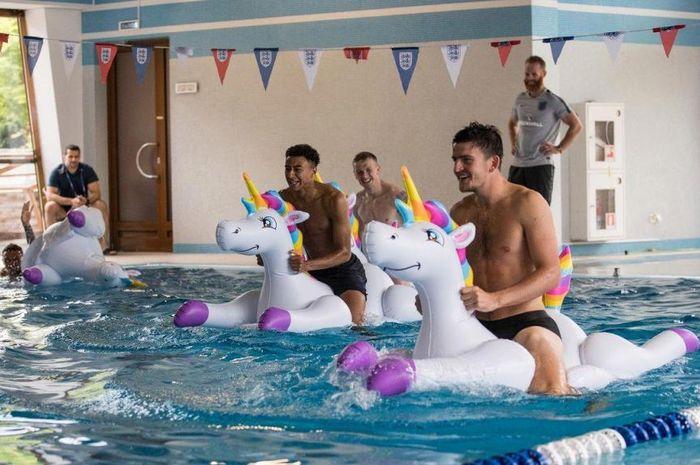 Pemain Timnas Inggris, Harry Maguire (kanan) dan Jesse Lingard lomba naik balon unicorn di kolam ren