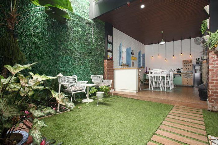 Ruang makan semi-terbuka bersebelahan dengan taman belakang.