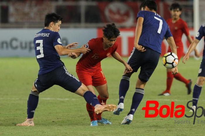 Penyerang timnas U-19 Indonesia, Hanis Saghara Putra diapit dua pemain timnas U-19 Jepang, Yuki Koba
