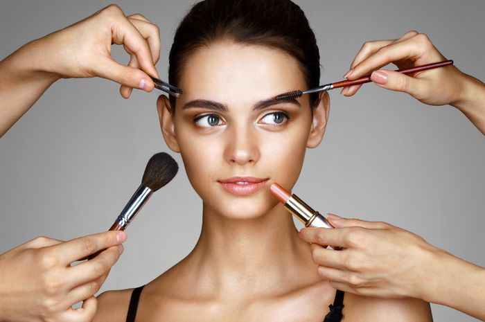 Beautiful girl surrounded by hands of makeup artists with brushes and lipstick near her face. Photo