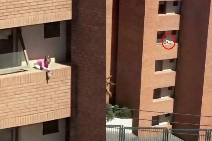 Anak kecil bermain di dinding tanpa pagar gedung bertingkat.