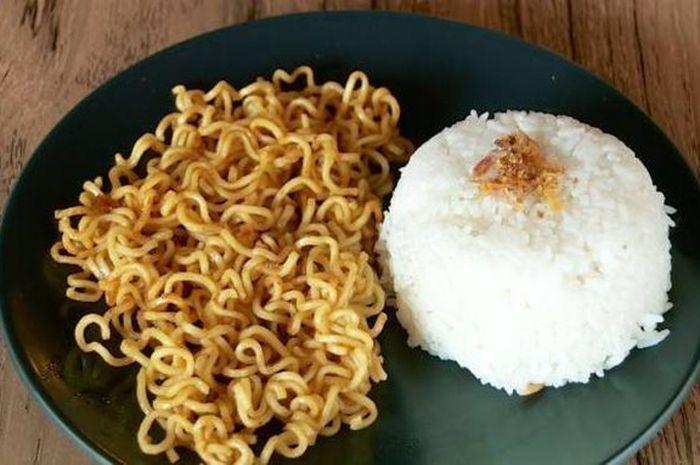 Makan mi instan dicampur nasi