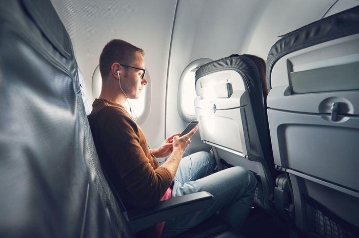 Penggunaan ponsel di pesawat dengan fitur airplane.