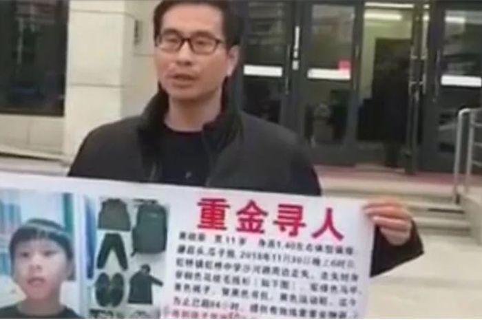 Ayah yang memegang poster anaknya yang hilang