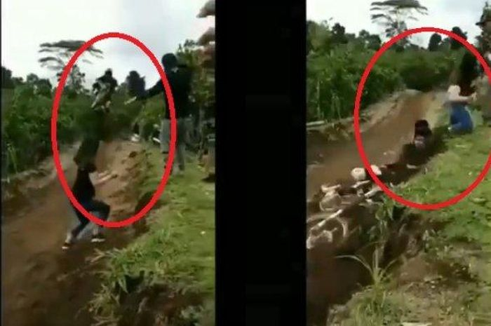 Seorang pebalap motocross jatuh karena menghindari dua wanita yang berjalan di tengah lintasan.