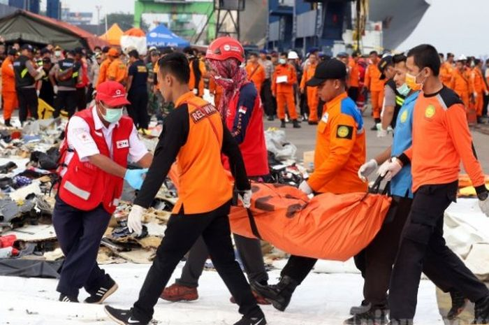Ilustrasi petugas gabungan membawa kantong berisi puing pesawat Lion Air JT 610 yang jatuh di perai