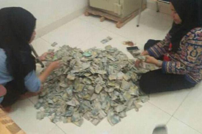 Dua karyawan yang sedang menghitung uang pecahan Rp 2.000 dari ibu Muspina