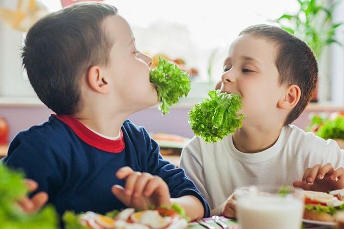 Anak-anak makan sayuran.